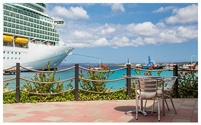 Image of a table and chairs at port looking at a cruise ship.