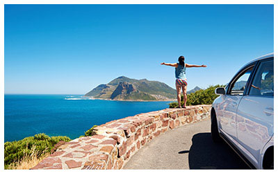 Image of woman on vacation with rental car.