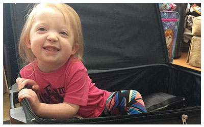 Image of a little girl playing in a suitcase.